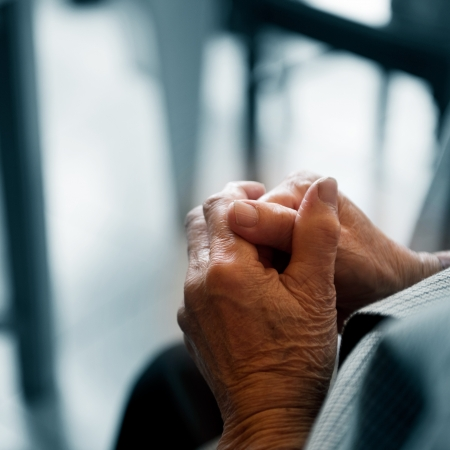 Old woman's hands clasped praying.