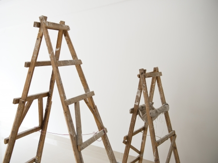Two wood ladders in front of white wall for home improve. photo