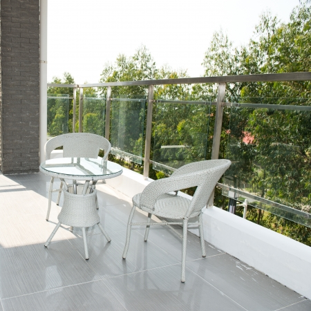 seating furniture: balcony with white table and chairs in a big house.