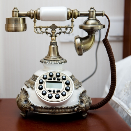 Luxury bedroom interior with vintage telephone on table. photo