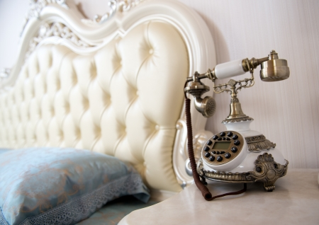 antique furniture: Luxury bedroom interior with vintage telephone on table. Stock Photo