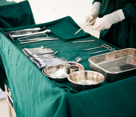 surgical glove: medical instruments with surgeons hand in operation room
