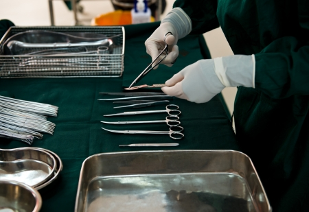 surgical coat: medical instruments with surgeons hand in operation room