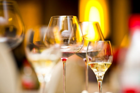 white wine glass: Glass of wine on table.  Stock Photo