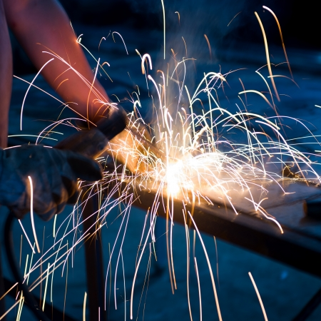 machinist: worker welding metal with sparks. Stock Photo