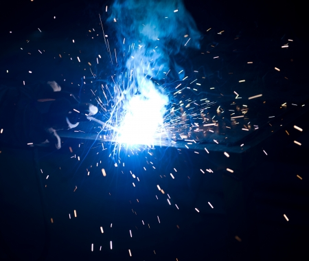 worker welding metal with sparks. Stock Photo