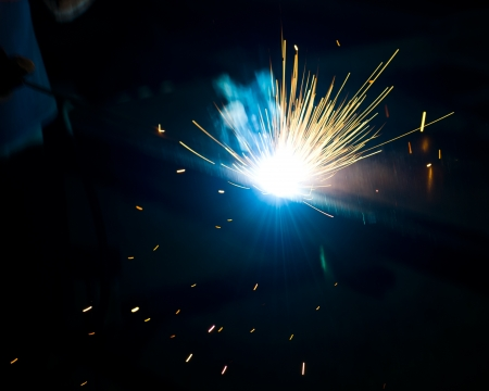 spark: worker welding metal with sparks. Stock Photo