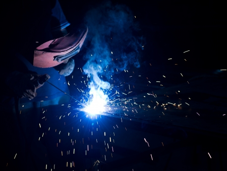acetylene: worker welding metal with sparks. Stock Photo