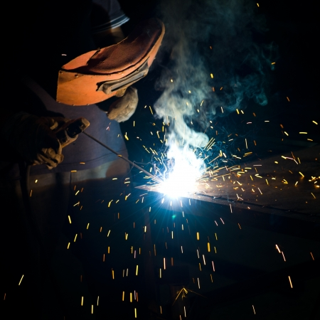 worker welding metal with sparks. photo
