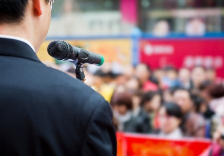 ビジネスの男性は、群衆の前でスピーチを作っています。