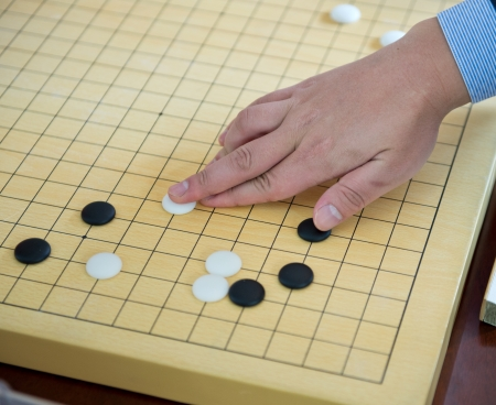 Detail of a woman playing chinese boardgame. photo