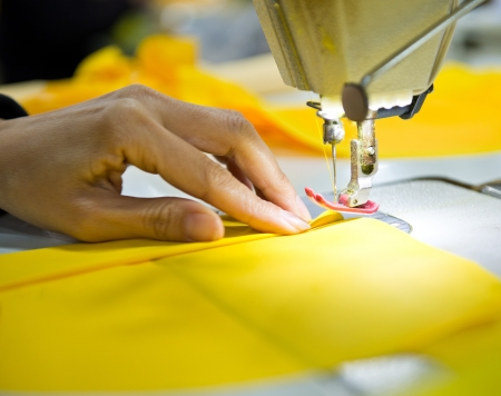 seamstress: Hand sewing a material on a machine.