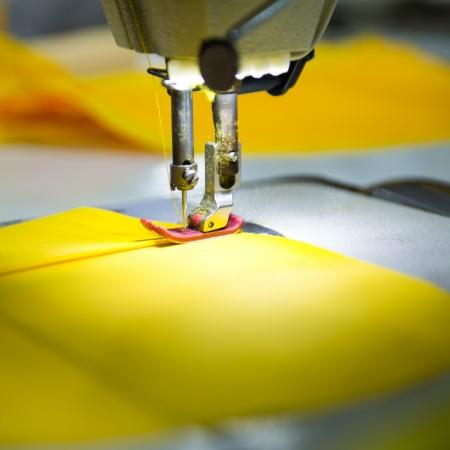 sartorial: Sewing machine with yellow cloth closeup Stock Photo