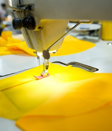 stitchwork: Sewing machine with yellow cloth closeup Stock Photo