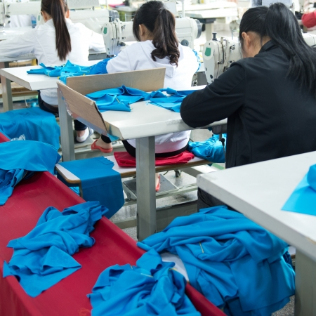 industria tessile: Dimensione industriale fabbrica tessile in Asia, lavoratori asiatici dietro macchine da cucire.