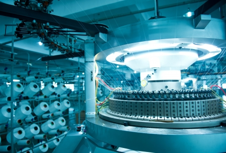 the textile industry: Textile industry - yarn spools on spinning machine in a textile factory Editorial