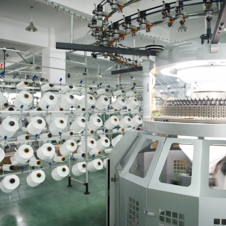 Textielindustrie - garenspoelen op spinnen machine in een textielfabriek Redactioneel