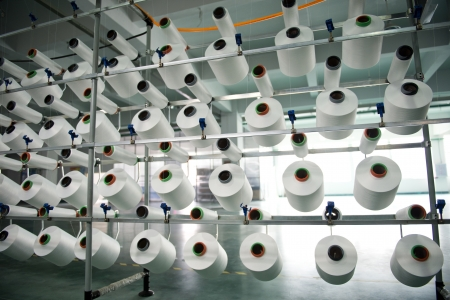 spinning factory: Textile industry - yarn spools on spinning machine in a textile factory Stock Photo