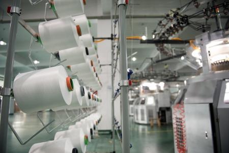 Industria textil - carretes de hilo en la máquina de hilar en una fábrica textil Foto de archivo - 20029363