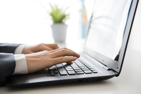 Close-up of human hands working on laptop. Stock Photo