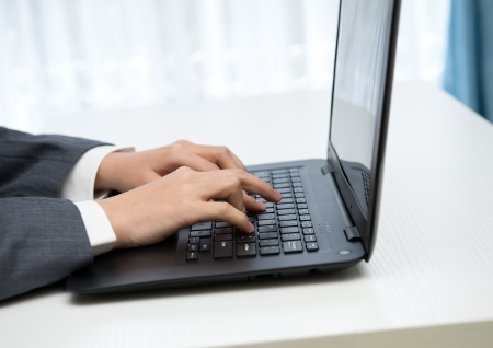 Close-up of human hands working on laptop. photo