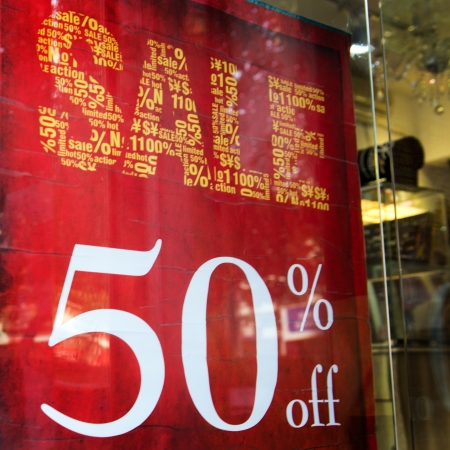 large windows: Red sale signs on shop wall, big reductions.