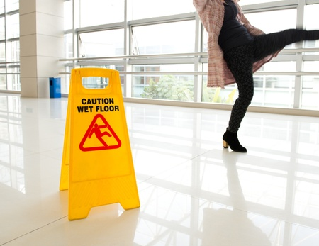 húmedo: La mujer se desliza junto al signo piso mojado
