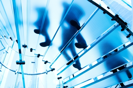 spiral stairs: Silhouette people on glass staircase Stock Photo