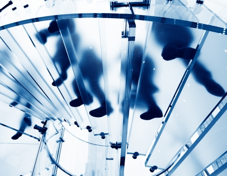 Silhouette people on glass staircase Stock Photo