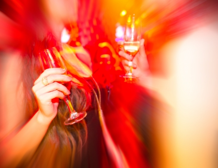 disco party: Two young woman in club with glass of wine in hand.