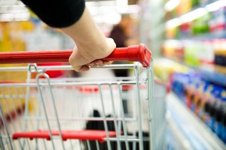 woman shopping cart: Closeup of woman with shopping cart.