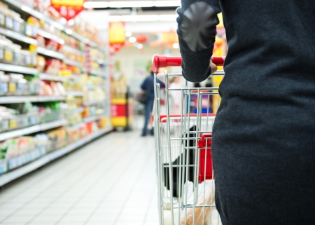 grocery trade: Closeup of woman with shopping cart.