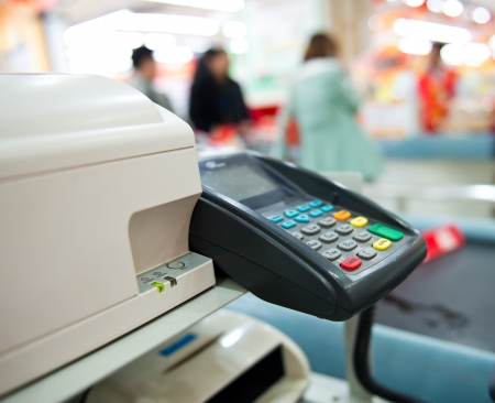 pos: Checkout counter with terminal in supermarket.