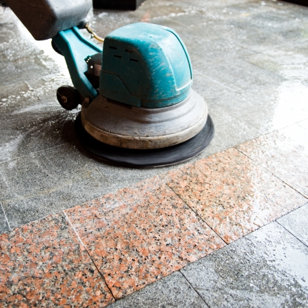 기계와 바닥을 청소하는 사람.