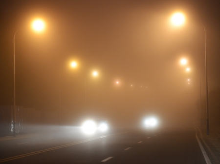 street shots: headlights of a car approaching in the thick fog at night.
