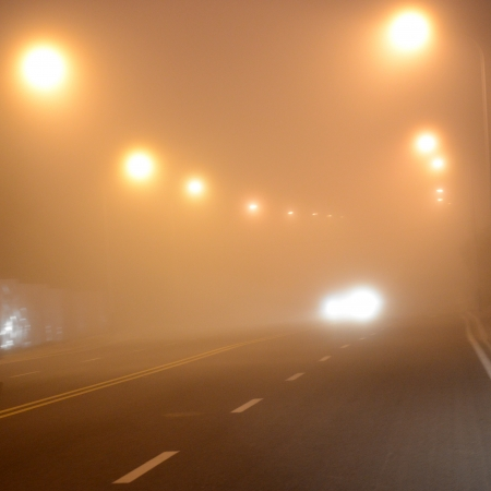 headlights: headlights of a car approaching in the thick fog at night.