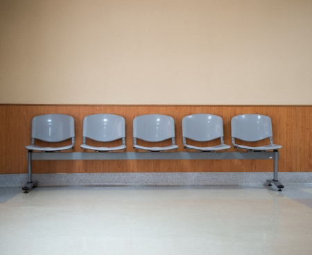 waiting area: Row of chairs in the hospital hallway.