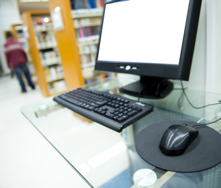 computer in a library with many books and shelves in the background. photo
