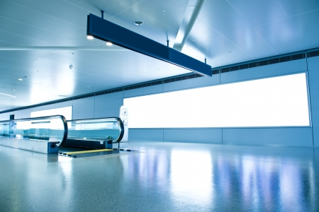 airport lounge: Blank billboard and modern escalator at a international airport