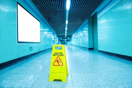 Wet floor caution sign on subway station floor. Stock Photo