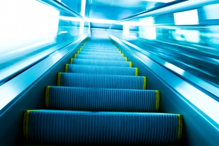 moving down: Low angle view looking to top of modern escalator with blue tone.