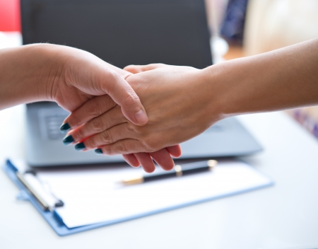 Handshake of business partners, laptop and paper in the background. photo