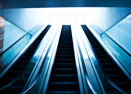 up and down: Low angle view looking to top of modern escalator with blue tone.