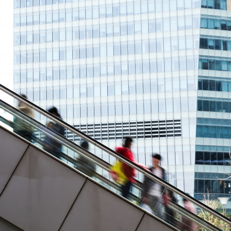 Business people using the escalator, with the background of modern office building. photo