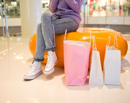 Woman sit at bench with bags in shopping mall photo