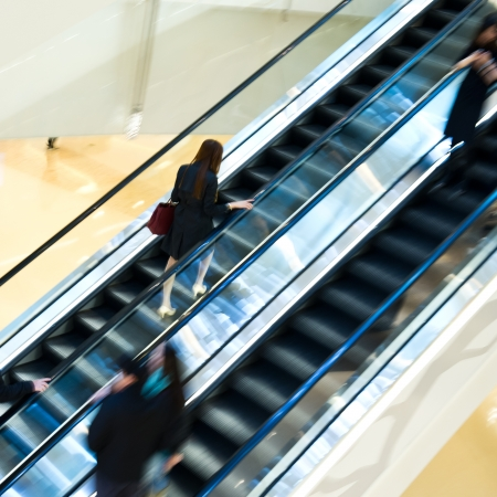 Business people walking on escalator.Blurred motion photo
