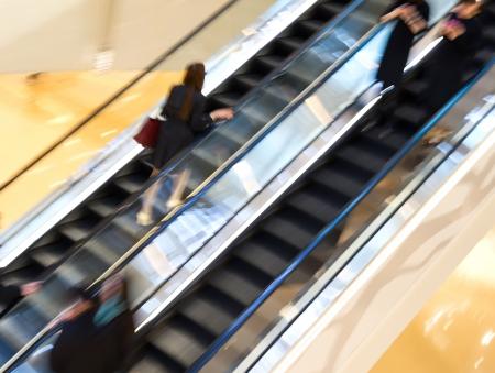 Business people walking on escalator.Blurred motion photo