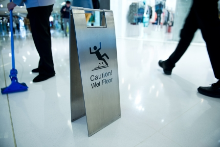 cleaning in progress, and wet floor caution sign besides. Stock Photo - 22994134