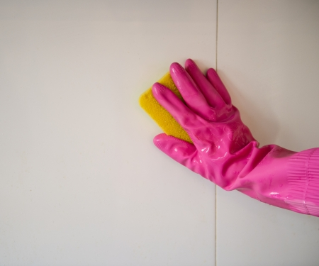 scrubbing up: Hand with sponge cleaning the bathroom tiles. Stock Photo
