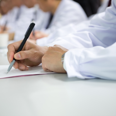medical team: Group of doctors writing at a conference.